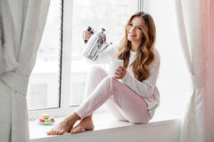 Женщина сидя на windowsill и лить чае или кофе от чайника стоковые изображения