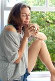Женщина сидя окном дома пахнуть свежей чашкой кофе Стоковое Изображение RF