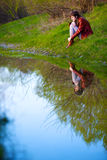 Женщина сидя около воды, Стоковое фото RF