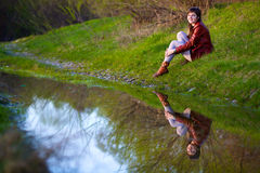 Женщина сидя около воды, Стоковое Изображение