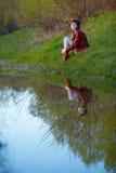 Женщина сидя около воды, Стоковое Изображение RF