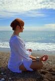Женщина сидя около моря Стоковые Изображения