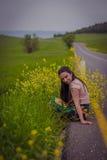 Женщина сидя около дороги Стоковые Фото
