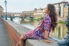 Женщина сидя около vecchio ponte в Флоренции Стоковая Фотография