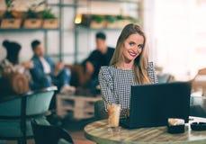 Женщина сидя перед открытым портативным компьютером в кафе Стоковая Фотография