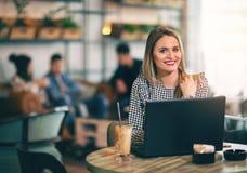 Женщина сидя перед открытым портативным компьютером в кафе Стоковое Фото