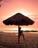 Женщина сидя под парасолем на пляже Стоковая Фотография
