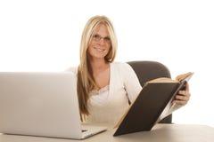 Женщина сидя с компьтер-книжкой и книгой и усмехаться Стоковое Фото