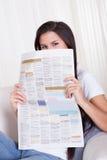 Женщина сидя читающ газету Стоковое Изображение RF