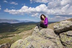 Женщина сидя na górze горы печатая в таблетке Стоковая Фотография