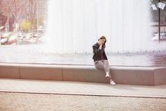 Женщина сидя waterworks и говоря на телефоне Стоковая Фотография RF