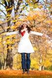 Женщина скача в парк осени стоковая фотография