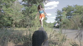 Женщина скача над автошинами сток-видео