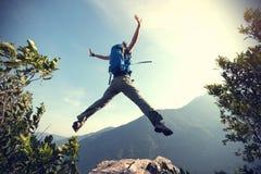 Женщина скача на край скалы стоковая фотография rf