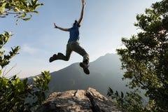 Женщина скача на край ` s скалы стоковая фотография