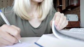 Женщина слегка ударяя через большую книгу, словарь и писать вне некоторую информацию, делая примечания, образование и студента сток-видео
