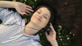 Женщина слушая к музыке лежа на траве акции видеоматериалы