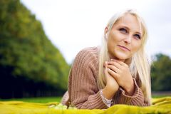 Женщина слушая к нот и ослабляя Стоковое Изображение