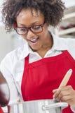 Женщина смешанной гонки Афро-американская варя кухню стоковая фотография