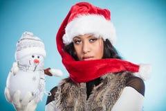 Женщина смешанной гонки в шляпе santa с маленьким снеговиком Стоковое фото RF
