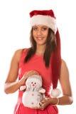 Женщина смешанной гонки в шляпе santa с маленьким снеговиком Стоковое Изображение