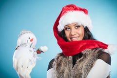 Женщина смешанной гонки в шляпе santa с маленьким снеговиком Стоковая Фотография RF