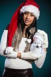 Женщина смешанной гонки в шляпе santa с маленьким снеговиком Стоковое Фото