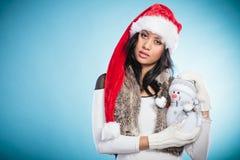 Женщина смешанной гонки в шляпе santa с маленьким снеговиком Стоковая Фотография