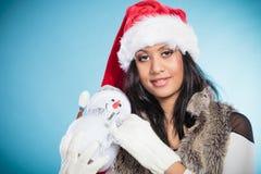 Женщина смешанной гонки в шляпе santa с маленьким снеговиком Стоковые Изображения