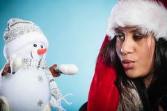 Женщина смешанной гонки в шляпе santa с маленьким снеговиком Стоковые Фотографии RF