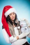 Женщина смешанной гонки в шляпе santa с маленьким снеговиком Стоковые Фото