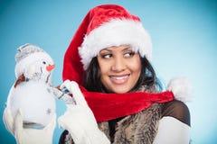 Женщина смешанной гонки в шляпе santa с маленьким снеговиком Стоковые Изображения RF