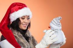 Женщина смешанной гонки в шляпе santa с маленьким снеговиком Стоковое Изображение RF