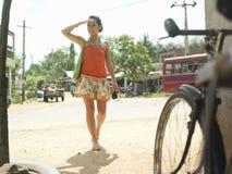 Женщина смешанной гонки идя на грязную улицу Стоковые Изображения RF