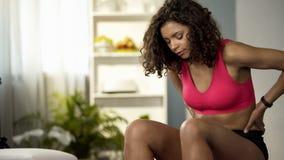 Женщина смешанной гонки протягивая ее назад после физических упражнений, боли в мышцах стоковое изображение rf