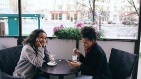 Женщина смешанной гонки Attrcative сидя на таблице в сотовом телефоне кафа улицы говоря пока ее друг занимаясь серфингом Стоковые Изображения RF