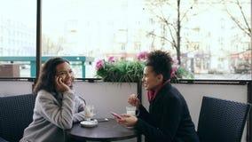 Женщина смешанной гонки Attrcative сидя на таблице в сотовом телефоне кафа улицы говоря пока ее друг занимаясь серфингом Стоковые Фотографии RF