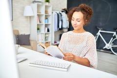Женщина Смешанн-гонки ослабляя на столе в домашнем офисе стоковое изображение rf