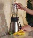 Женщина смешивает киви, бананы и молоко миндалины для того чтобы сделать здоровый коктеиль плодоовощ Стоковое Изображение RF