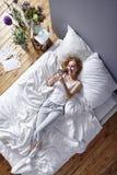 Женщина смеясь над в кровати Стоковое Фото