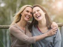 Женщина 2 смеясь над и обнимая одином другого outdoors Стоковая Фотография RF