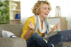 Женщина смеясь с наслаждением пока смотрящ телевизионный сюжет стоковые фотографии rf