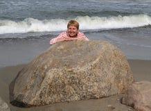 Женщина смотрит вне из-за камня на seashore Стоковое Изображение