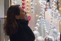 Женщина смотрит в выставк-окне магазина стоковое изображение