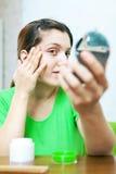 Женщина смотрит на ее коже Стоковая Фотография RF
