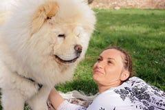 Женщина смотрит собаку чау-чау чау-чау с влюбленностью Стоковая Фотография