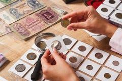 Женщина смотрит старую монетку Стоковая Фотография RF