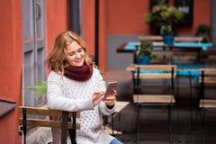 Женщина смотрит телефон Стоковые Изображения RF