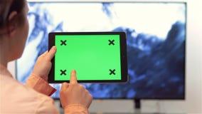 Женщина смотрит телевидение пока держащ и выстукивающ на приборе планшета сток-видео
