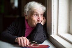 Женщина смотрит уныло вне окно стоковая фотография rf